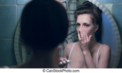 Woman smears a cream front of the mirror