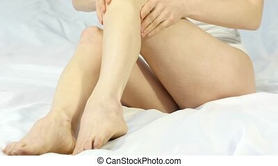 woman smears cream on her legs. foot care concept,...
