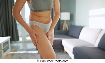 Woman smears her leg with anti-cellulite gel and does self-massage. Concept of striving to meet generally accepted beauty standards