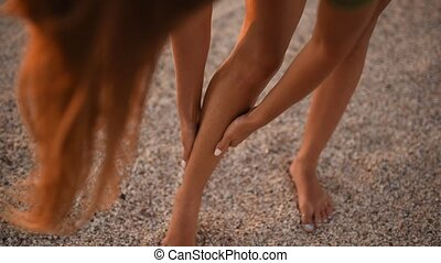 skinny slender young woman smears moisturizing sunscreen body cream on her legs on the beach in summer