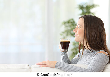 Woman smelling a cup of coffee at home