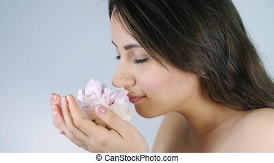 Woman smelling flower on white background - Young attractive...