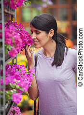 Woman smelling flowers in garden center