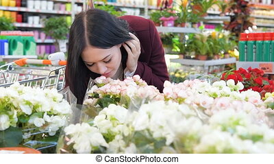 Woman smelling flowers in greenhouse in Slow Motion -...