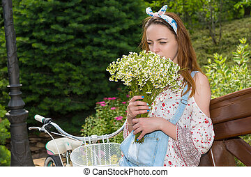 Woman smelling flowers near bike