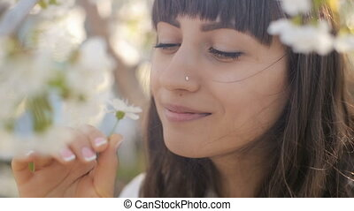 Woman smelling flowers on a branch