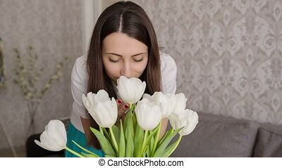 Woman Smelling Her Vase Of Tulips