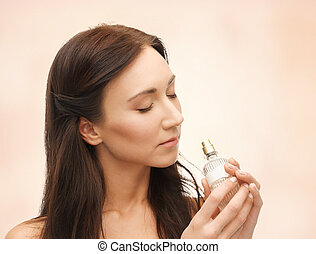 woman smelling perfume - picture of young beautiful woman...