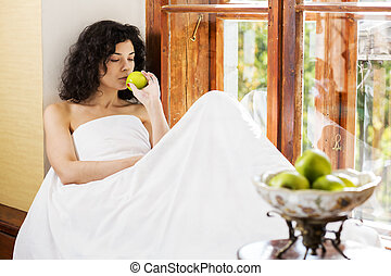 Woman smells green apple on wooden sill - Pretty woman...