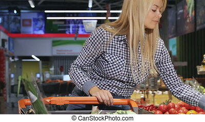 Woman smells the tomato at the supermarket