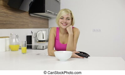 woman smile laugh watching tv hold remote control eat corn flakes, girl changing channels modern kitchen