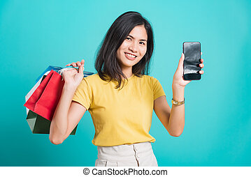 Portrait happy Asian beautiful young woman smile white teeth standing wear yellow t-shirt, She holding shopping bags and using a mobile phone, studio shot on blue background with copy space for text