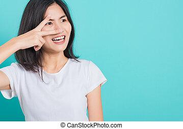 woman smile wear white t-shirt standing showing two finger making v-sign near eye