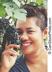 Woman smile with grapes in vineyard