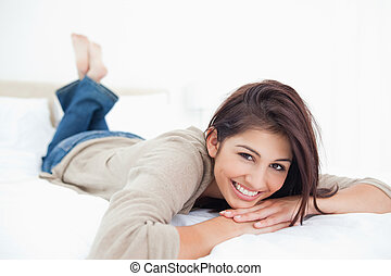 Woman smiles on the bed with crossed feet and her head being propped up by her hands.