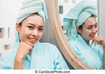 woman smiles seeing the camera standing next to the mirror with a touch of clean skin