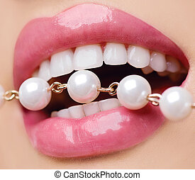Woman smiles showing white teeth, holding a pearly necklace into the mouth