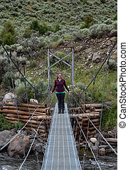 Woman Smiles While Standing on Footbridge