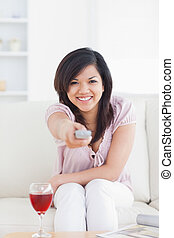 Woman smiling and holding a television remote