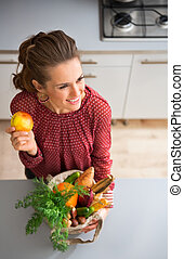 Woman smiling and holding apple and fall vegetables in kitchen