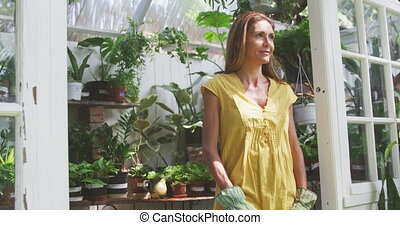 Woman smiling and looking at camera in a greenhouse