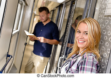 Woman smiling and man reading in train
