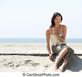 Woman smiling and relaxing at the beach