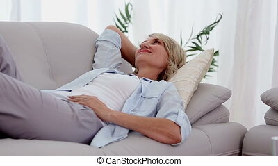 Woman smiling and relaxing on sofa