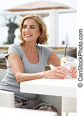 Woman smiling and relaxing with a drink of water outdoors