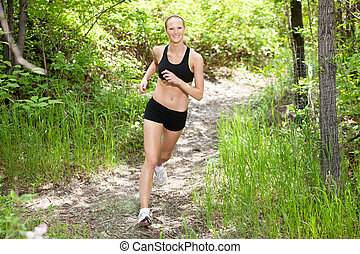 Woman smiling and running in forest
