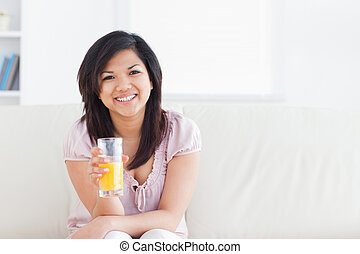 Woman smiling and sitting in a couch while holding a glass of orange juice in a living room