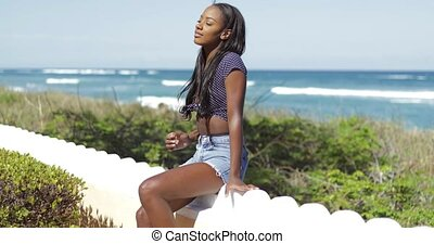 Woman smiling and sitting on fence - Attractive young black...