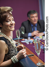 Woman smiling and waiting for roulette wheel