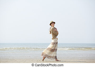 Woman smiling and walking on the beach
