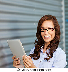 Woman smiling and working on the ipad - Image of a female...