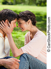 Woman smiling as she looks at her friend while they touch their heads together in a park