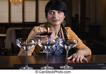 Woman smiling as she sits drinking at the bar