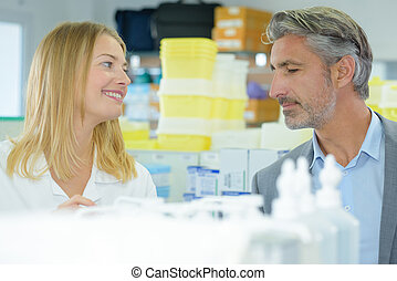 Woman smiling at man over medical supplies
