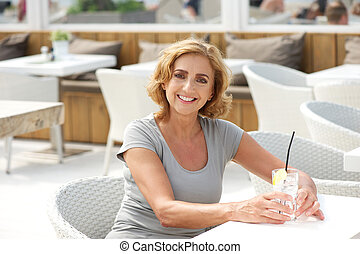 Woman smiling at restaurant with glass of water