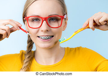 Woman smiling cleaning teeth with braces - Dentist and...