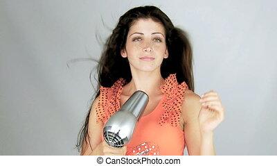 Woman smiling drying long hair blow