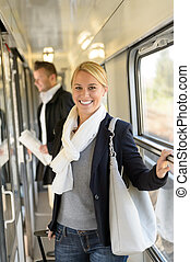 Woman smiling in train hall with luggage