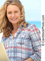 Woman smiling on laptop.