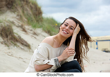 Woman smiling outdoors with hand in hair