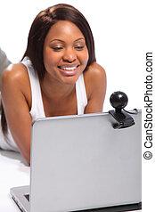 Woman smiling to webcam - Beautiful black woman on floor...