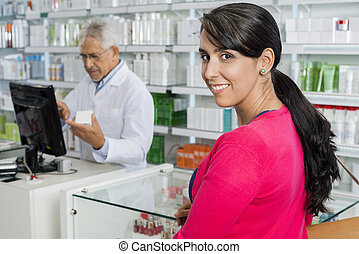 Woman Smiling While Chemist Working In Pharmacy