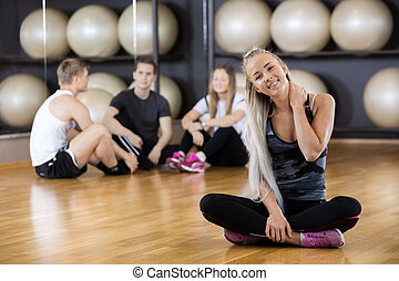 Woman Smiling While Friends Sitting In Gym
