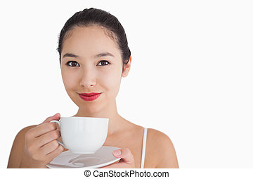 Woman smiling while holding a cup