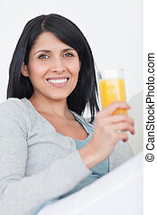 Woman smiling while holding a glass full of orange juice