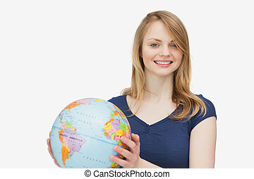 Woman smiling while holding a globe